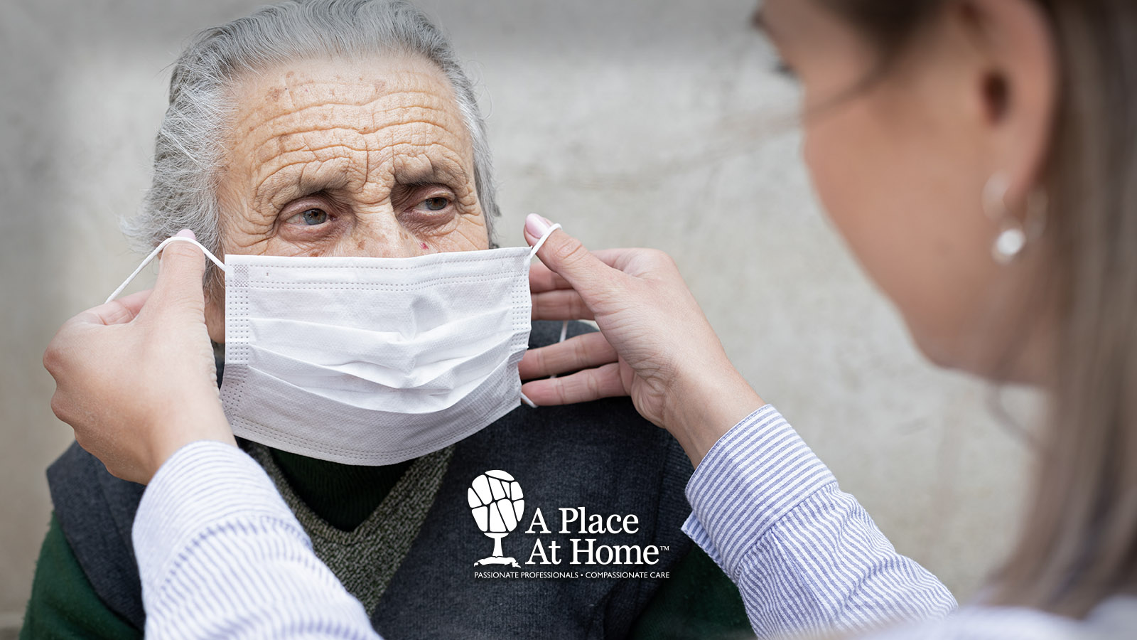 A caregiver helping place a mask on a senior.
